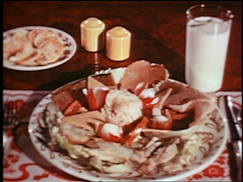 vidéos et rushes de 1948 close up lunch food on plates + glass of milk on table / industrial - plein