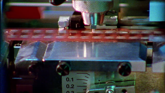 Close up machine punching holes in sheet of computer chips