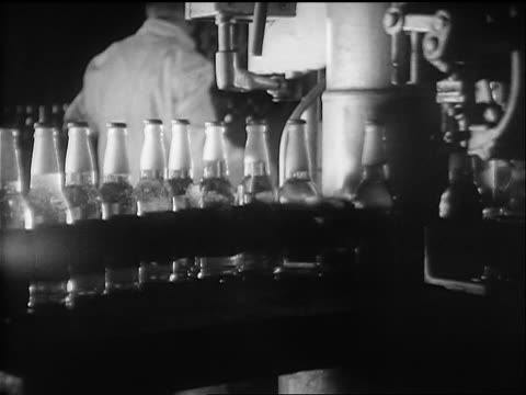 b/w 1933 close up machine putting caps on bottles of beer on conveyor in factory / man in background - モノクロ点の映像素材/bロール
