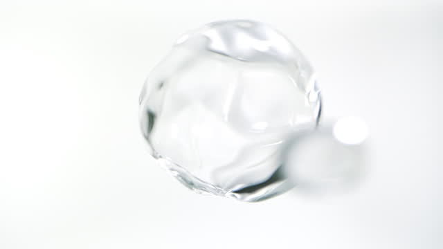 close up macro and super slow motion of floating clear water drops against a white background - molecule stock videos & royalty-free footage