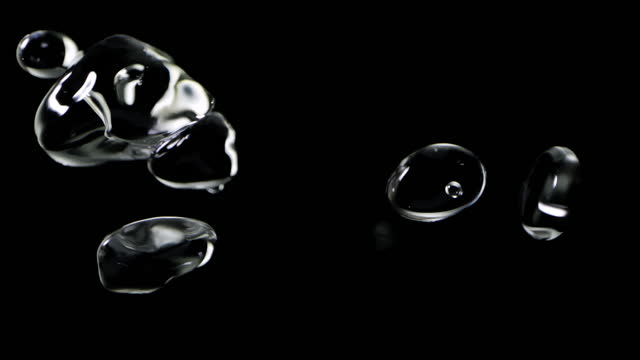 close up macro and super slow motion of floating clear water drops isolated on black background - black colour stock videos & royalty-free footage