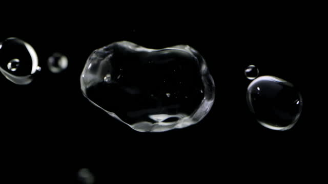 close up macro and super slow motion of floating clear water drops isolated on black background - molecule stock videos & royalty-free footage