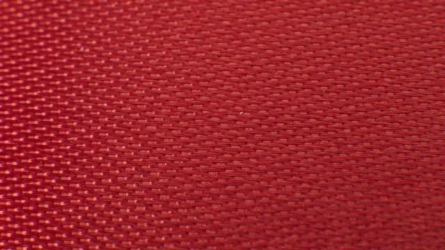 Fermez la texture de tissu macro ruban rouge. Motif de fond de textile