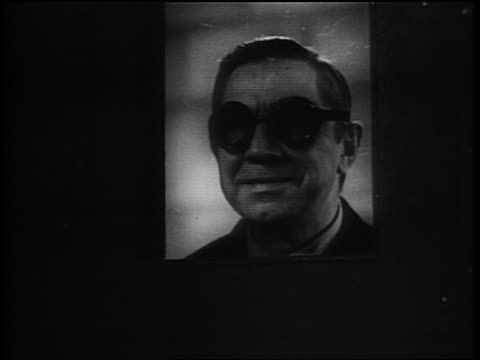 vidéos et rushes de b/w 1940 close up mad scientist in goggles watching flashing lights thru window - mystère