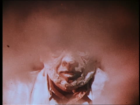 vídeos de stock, filmes e b-roll de close up mad scientist spreading synthetic flesh on his face + becoming a monster / smoke in foreground - monstro