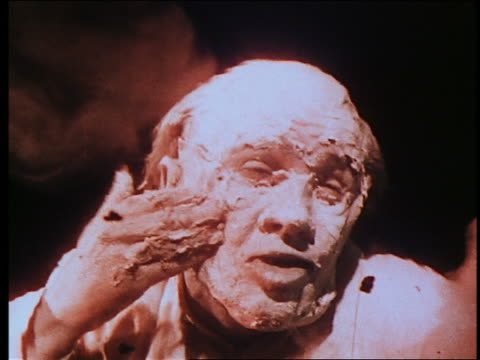 vídeos de stock, filmes e b-roll de close up mad scientist spreading synthetic flesh on his face + becoming a monster / seen from under water - feiura