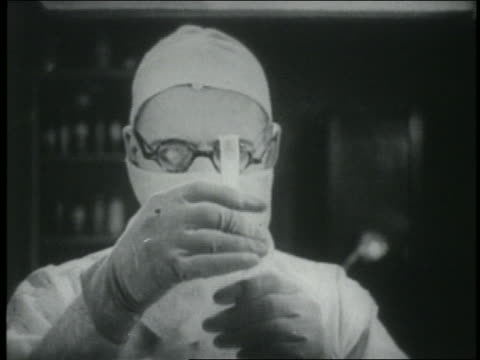 b/w 1915 close up mad scientist wearing surgical mask holding test tube with smoke emerging / silent serial - scientist stock videos & royalty-free footage