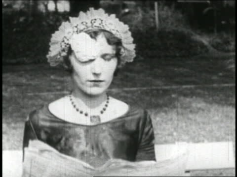 b/w 1928 close up maid reading + getting hit in face by ice cream thrown from offscreen / short - collaboratore domestico video stock e b–roll