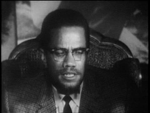 close up malcolm x with eyeglasses sitting in chair + speaking about africa / documentary - black civil rights stock videos & royalty-free footage