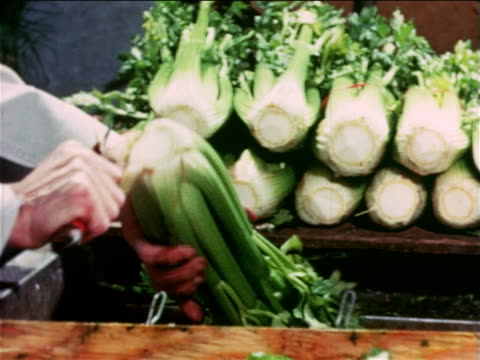 vídeos y material grabado en eventos de stock de 1965 close up male grocer's hands cutting off bottom of stalk of celery in store / educational - apio