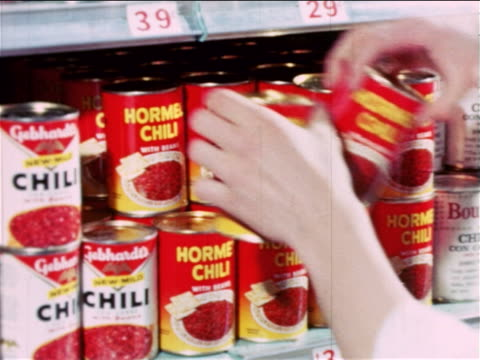 vídeos de stock, filmes e b-roll de 1965 close up male grocer's hands putting cans of hormel chili on shelf of grocery store / educational - 1965