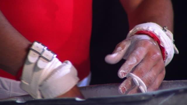 vídeos de stock, filmes e b-roll de close up male gymnast chalking hands - giz equipamento esportivo