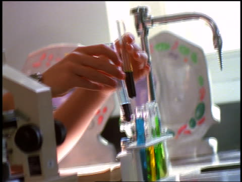 stockvideo's en b-roll-footage met canted close up male high school student pouring liquid from test tubes into test tube in laboratory - alleen één tienerjongen