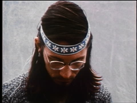 1970 close up male hippie in eyeglasses + headband rolling head with eyes closed / biofeedback