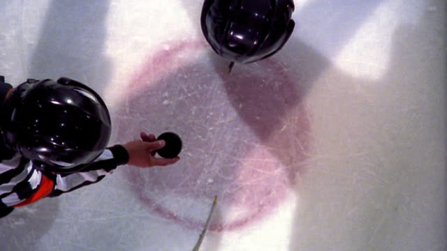 OVERHEAD close up male referee drops ice hockey puck in face off/ opposing male players battle for control