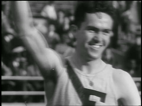 B/W 1933 close up male runner raising arm in air + smiling after race / Philadelphia / newsreel