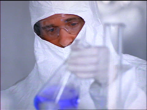 close up PAN male scientist in white clean suit shakes + examines blue liquid in glass beaker