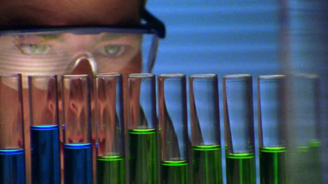 close up male scientist wearing safety goggles looking at blue + green liquids in test tubes