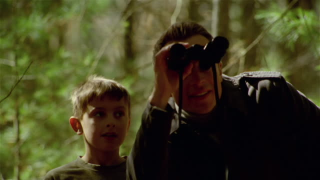 close up man and boy looking through binoculars in woods - binoculars stock videos & royalty-free footage