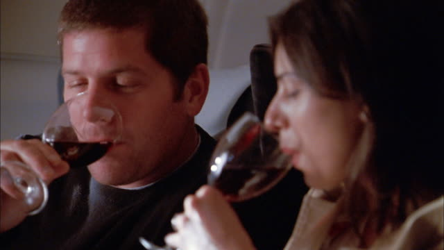 Close up man and woman drinking wine + talking on airplane