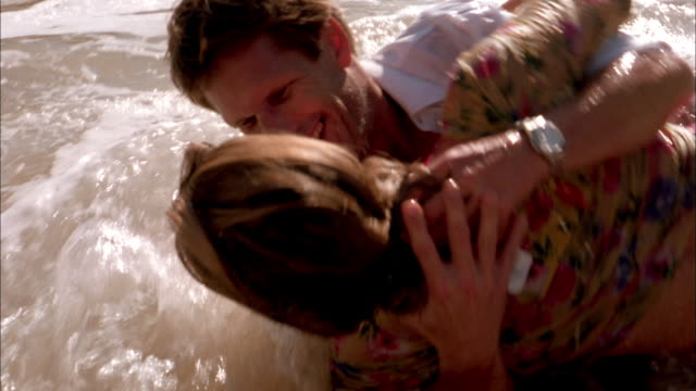 close up man and woman embracing + rolling in surf on beach - wet stock videos & royalty-free footage