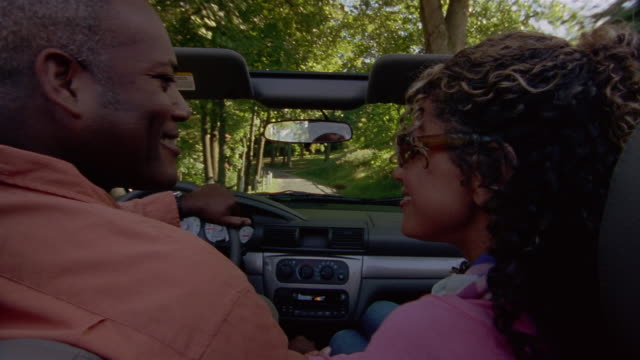 close up man and woman smiling at each other + riding on tree-lined road in convertible - convertible stock videos & royalty-free footage
