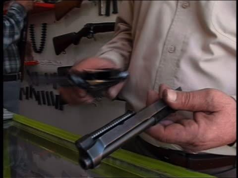 2003 close up man assembling handgun and testing in gun store / iraq / audio - 陳列ケース点の映像素材/bロール