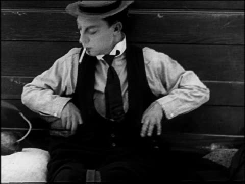 b/w 1922 close up man at reins of wagon using bomb to light cigarette / feature - buster keaton stock videos and b-roll footage