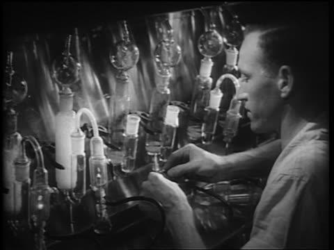 b/w 1952 close up man attaching hose to bunsen burner in laboratory - bunsen burner stock videos & royalty-free footage