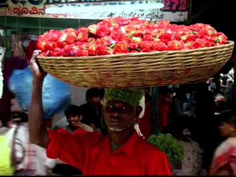 Close up man carrying basket of flowers on his head