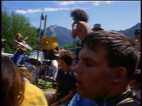 vídeos de stock e filmes b-roll de 1968 close up man dancing with eyes closed / band playing on stage in background / tapia park ca / newsreel - love in