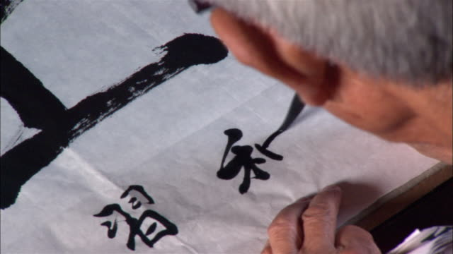 vídeos de stock, filmes e b-roll de close up man drawing characters on paper with calligraphy pen - língua chinesa