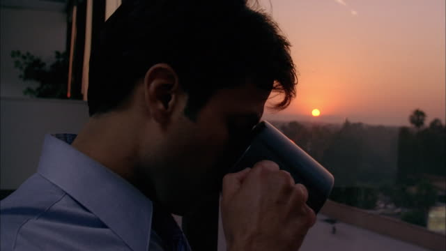 close up man drinking coffee and looking out window at sunset - mug stock videos and b-roll footage