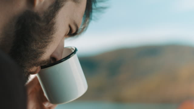 vídeos de stock e filmes b-roll de close up, man drinking coffee and reading at camping trip - café bebida