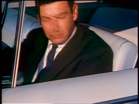 1959 close up man driving car looking over shoulder out window / educational