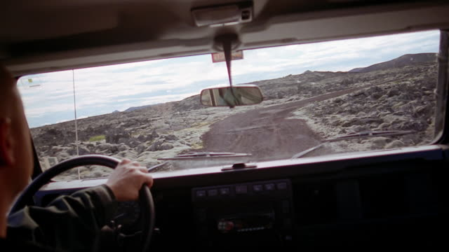 Close up man driving Land Rover through lava field near the Blue Lagoon (Blaa Loninu) / Iceland