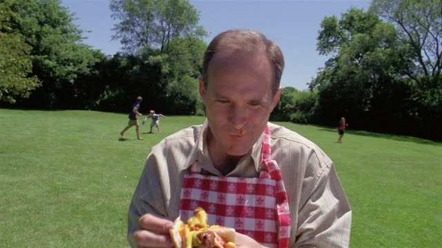 close up man eating sausage sandwich with children playing in background - hot dog stock videos & royalty-free footage