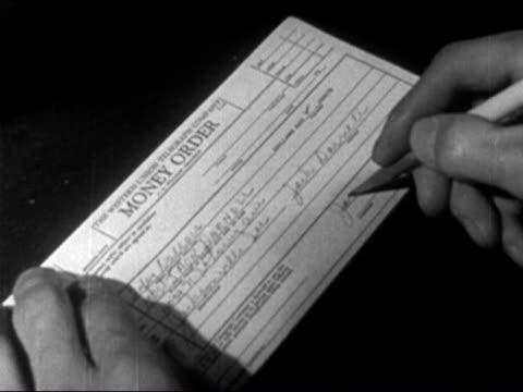 vídeos de stock e filmes b-roll de 1946 close up man filling out western union money order - só homens maduros