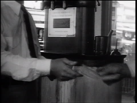 b/w 1932 close up man handing scrip to male gas attendant + rolling up wad of bills + walking away - filling station attendant stock videos & royalty-free footage