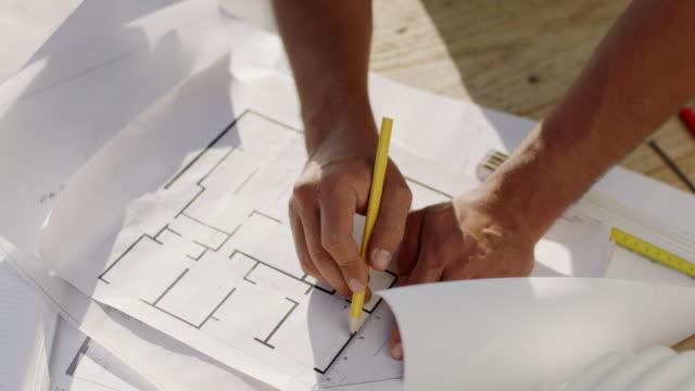 Nahaufnahme, Mannhände zeichnen Baupläne auf Tisch