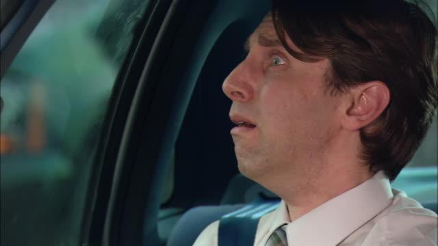 Close up man having nervous breakdown in backseat of car / pan to embarrassed carpool passengers