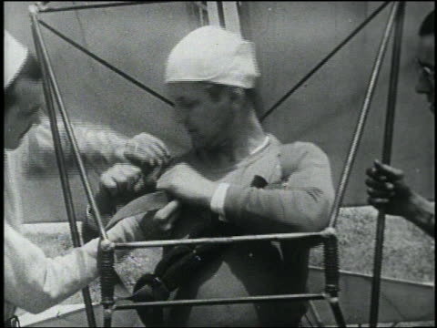 b/w close up man helps other man with early hang glider tighten strap on shoulder - 発明家点の映像素材/bロール