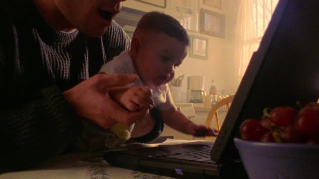 close up man holding baby on lap helping baby hit key on laptop at kitchen table - 2000 stock videos and b-roll footage