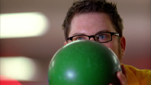 close up man holding bowling ball in front of face and bowling - bowling ball stock videos & royalty-free footage