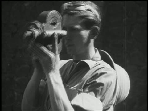stockvideo's en b-roll-footage met 1932 close up man holding film camera up to face / turning slowly - ontdekkingsreiziger
