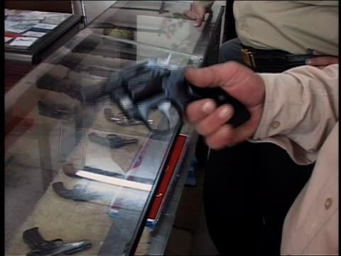 close up man holding small handgun and testing trigger in gun store / iraq audio - skåp med glasdörrar bildbanksvideor och videomaterial från bakom kulisserna