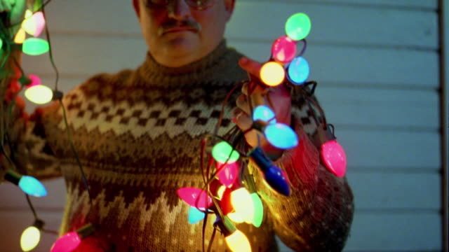 close up man holding string of christmas lights in both hands - pullover stock videos & royalty-free footage