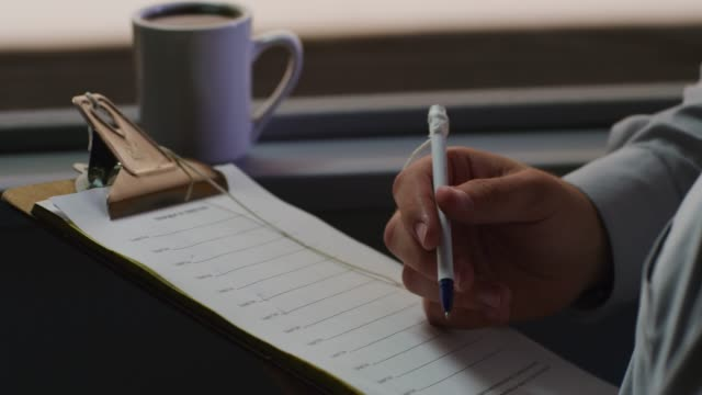 close up; man holds a clipboard with a checklist in right hand; a ball point pen in the left; cup of coffee in the background. - checklist stock videos & royalty-free footage