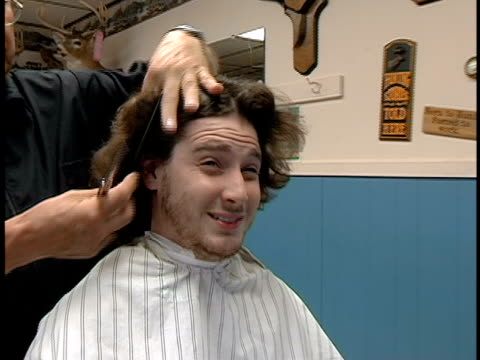 Close up man in barber shop making faces as barber cuts his long hair