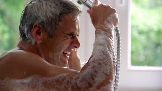 close up man in bathtub using hand held shower and washing his face + hair - taking a bath stock videos & royalty-free footage